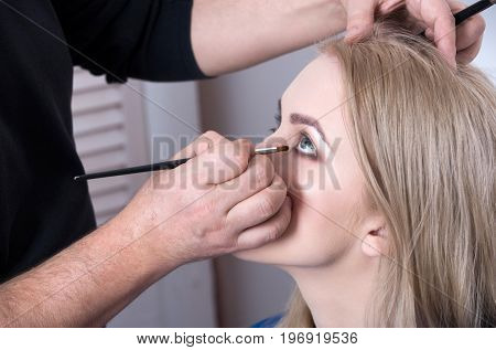 Visagiste Applying Eye Makeup On Girl Face With Brush