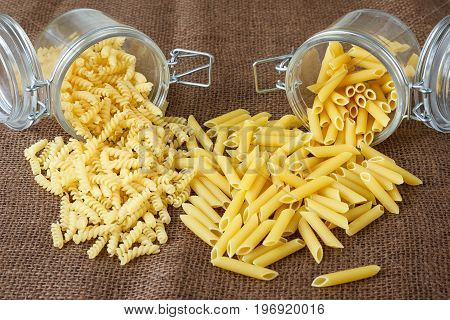Italian Pasta - Penne And Fusilli In Glass Jar On Brown Background