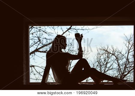 Girl drink from cup in morning. Silhouette of sexy woman on window sill. Beauty and fashion. Fashion model posing. Woman with in dress laying at window.