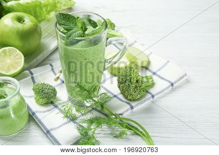 Glass of fresh juice and ingredients on wooden background