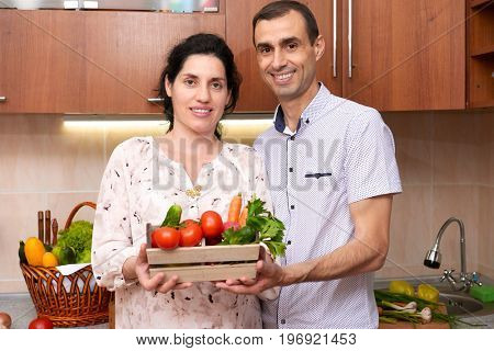 couple in kitchen interior with box of fresh fruits and vegetables, healthy food concept, pregnant woman and man