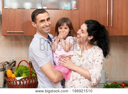 family portrait in kitchen interior with fresh fruits and vegetables, healthy food concept, pregnant woman, man and child girl