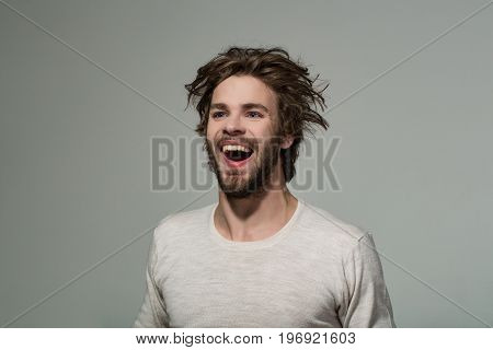happy man with long stylish uncombed hair and smiling bearded man on grey background morning and barbershop fashion