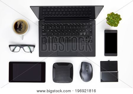 Overhead view of various devices arranged with coffee cup, plant and eyeglasses on white office desk