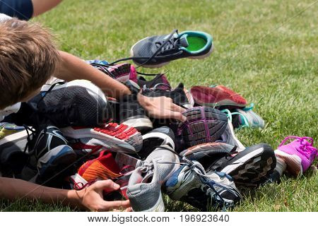 A young athlete runs into a pile of running shoes breaking up the pile for a game called the shoe relay at a running camp