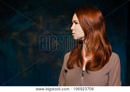 Dissatisfaction red-haired girl in brown shirt. beauty model woman with luxurious red hair. hairstyle. holiday makeup