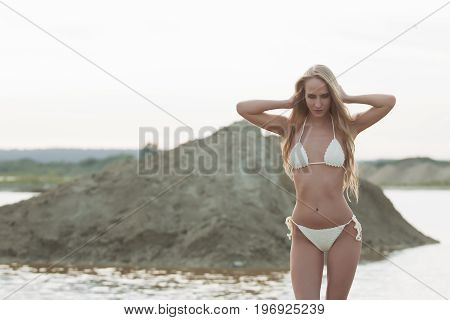 Girl on the sandy beach in a bathing suit.