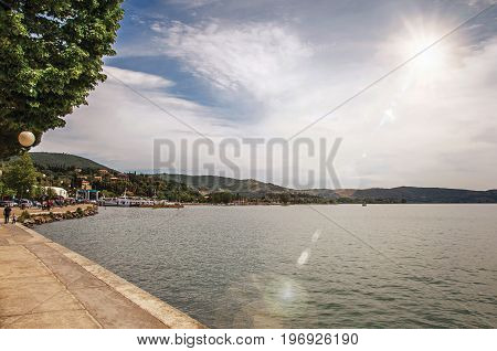 Overview of the hamlet and its promenade on the shores of Lake Trasimeno, a picturesque lake near Perugia. Located in Umbria region, central Italy. Retouched photo