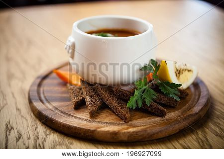 Saltwort russian beef, pork and sausage soup solyanka with lemon, salami in plate on wood background
