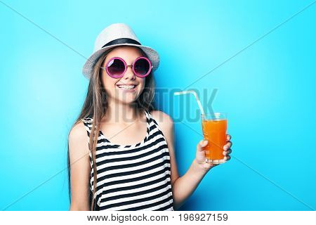 Portrait Of Beautiful Girl With Sunglasses And Glass Of Juice On Blue Background