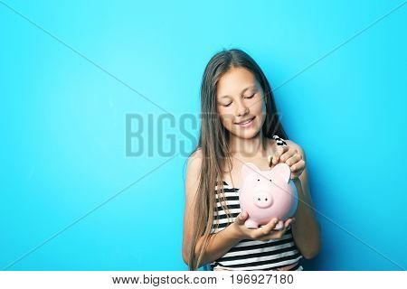 Portrait of beautiful girl with piggy bank on blue background