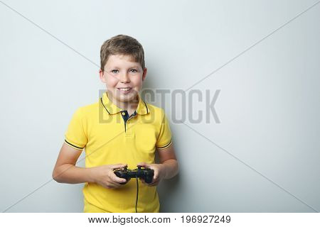 Portrait Of Young Boy With Joystick On Grey Background