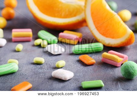 Different Chewing Gums With Orange On Grey Wooden Table