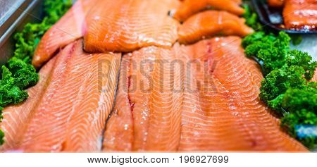 Seafood Stand With Cuts And Filets Of Salmon On Ice With Kale Leaves