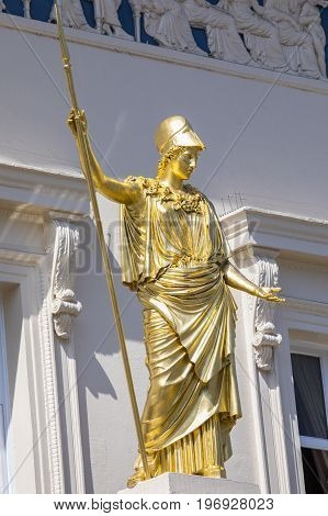 A golden statue of Athena the classical goddess of wisdom outside the famous Athenaeum Club in central London UK.