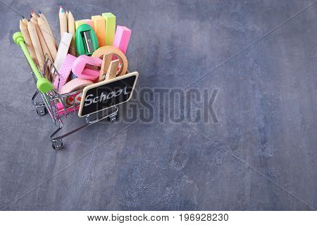 Shopping Cart With School Supplies On Grey Wooden Table