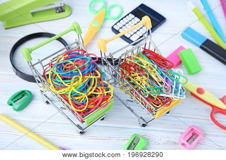 Shopping Carts With Rubber Bands And Paperclips On Wooden Table