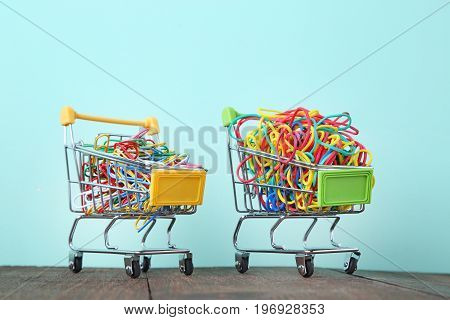 Shopping Carts With Rubber Bands And Paperclips On Mint Background