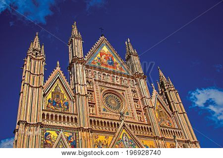 Facade details of the opulent and monumental Orvieto Cathedral (Duomo) under sunny blue sky in Orvieto, a pleasant and well preserved medieval town. Located in Umbria, central Italy. Retouched photo