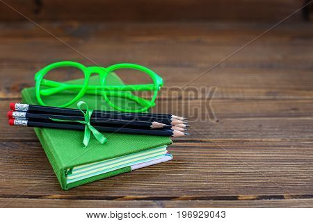 Background with pencils and glasses and a book. The concept is back to school.