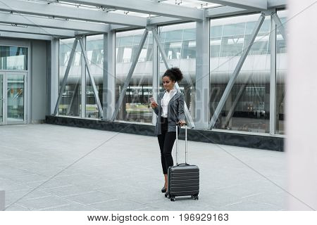 Young woman with luggage and cell phone preparing for business trip