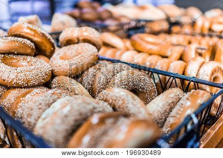 Closeup of many bagels in bakery on display