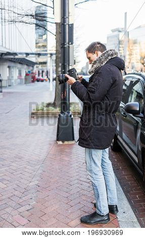 Street photographer with DSLR camera on sidewalk in winter