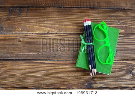 Background with pencils and glasses and a book. Top view. The concept is back to school.
