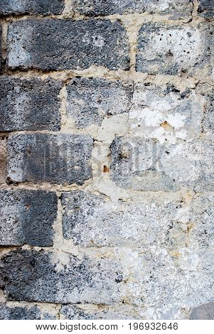 Verticalold wall of black and white brick with rough texture as background.