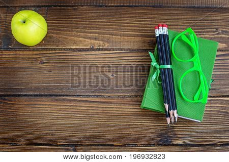 Pencils and glasses a book and an apple on a wooden background. Top view. The concept is back to school.