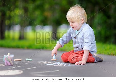 Happy Little Kid Boy Drawing With Colored Chalk On Asphalt.
