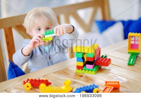 Little Boy Playing With Colorful Plastic Blocks At Kindergarten.