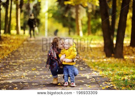 Father and his toddler son walking in autumn forest. Family outdoor leisure in park.