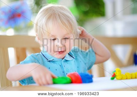 Creative Boy Playing With Colorful Modeling Clay At Kindergarten