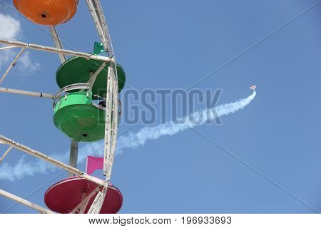 A ferries wheel with a contrail from a plane