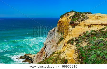Yellow Rocks And Sand On Portuguese Coastline, Vivid Ocean Water