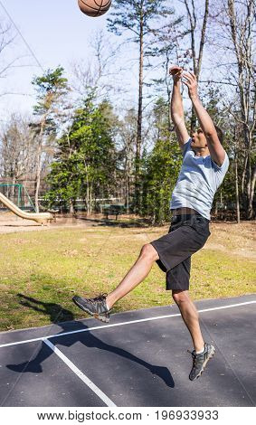Young Fit Muscular Man Jumping Up Throwing Basketball Into Hoop