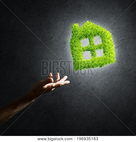 Close of businessman hand and green house icon as symbol of save construction