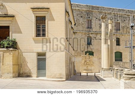 Ordnance street with the ruins of the demolished Opera House at Pjazza Teatru Rjal (Royal Theatre Square) with the baroque water well at the wall of the House of the Annona in Valletta Malta