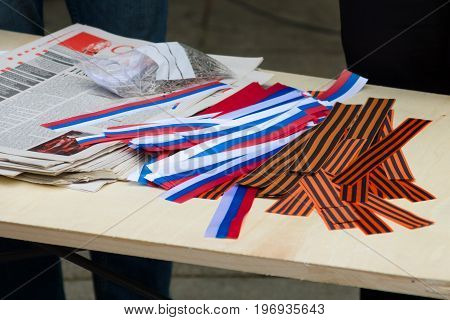 BERLIN - MAY 08 2015: Victory in Europe Day. Treptower Park. Free distribution of St. George ribbons and ribbons with tricolor - the national colors of Russia.