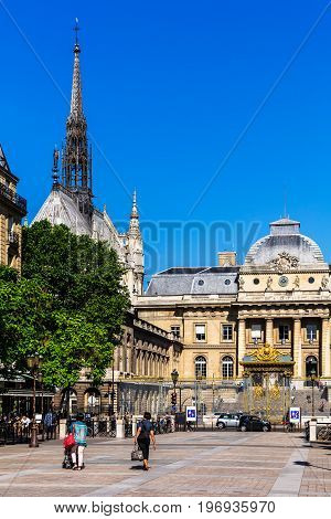 Paris France - July 04 2017: Tourists in front of the Palace of Justice (Palais de Justice) with decorative wrought-iron lattice fence. The Holy Chapel (Sainte Chapelle) is a royal chapel in the gothic style.