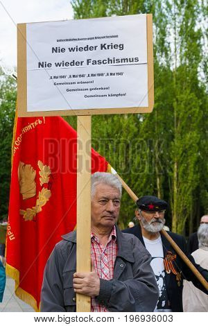 BERLIN - MAY 08 2015: Victory in Europe Day. Treptower Park. Communist activists at the memorable event. Text in German: No War! No fascism!