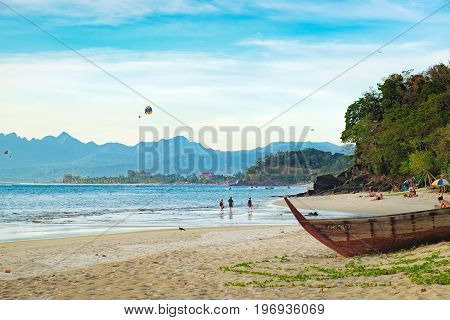 Langkawi, Malaysia - February 14, 2016: Seascape with islands on the horizon old wooden fishing boat on the beach in the foreground. Paragliders at sunny day summer adventure in Pantai Tengah Beach