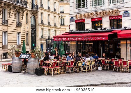 Paris France - June 16 2017: A traditional restaurant A La Place St Georges in Paris in St.Georges Square. Parisians and tourists enjoy food and drinks on the terrace in the summer day.