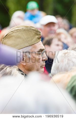 BERLIN - MAY 08 2015: Victory in Europe Day. Treptower Park. An elderly man in a soldier's forage cap listens participants commemorative ceremony.
