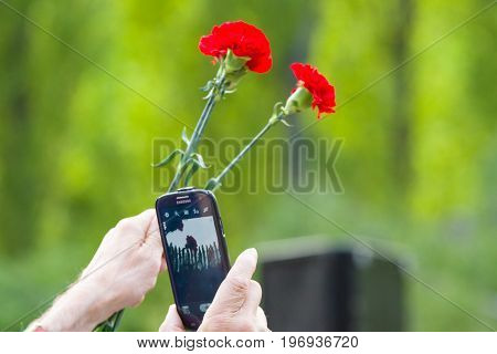 BERLIN - MAY 08 2015: Victory in Europe Day. Treptower Park. Red carnations and mobile phone. Member of the memorable events photographs at arm's length.