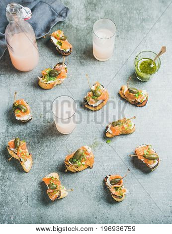 Crostini with smoked salmon, pesto sauce, watercress and capers and pink grapefruit cocktails over grey background, top view. Party, catering or fingerfood concept