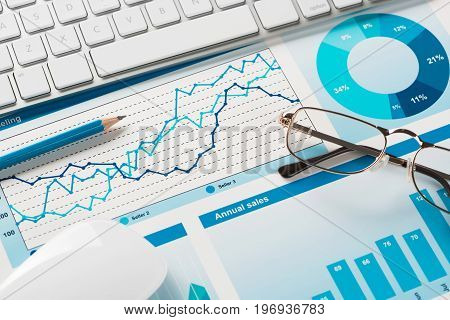 Business workplace with keyboard mouse and papers with graphs and diagrams