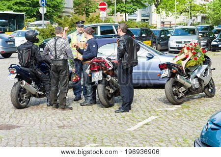 BERLIN - MAY 09, 2015: Numerous police officers ensure order and peace at the event. A police officer talks to bikers.