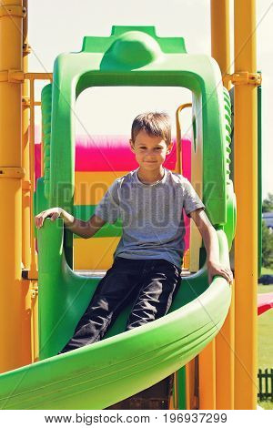 Little boy having fun playing on a playground outdoors in summer